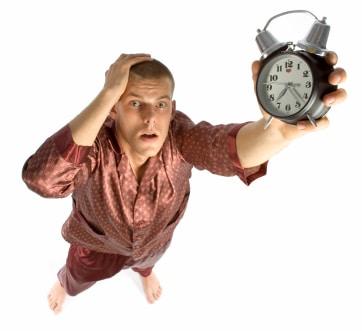 Hombre en pijama reloj despertador